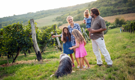 Wine grower family tasting wine in vineyard