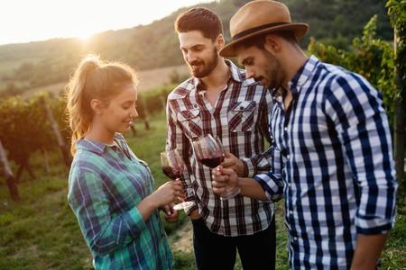 Happy people tasting wine in vineyard