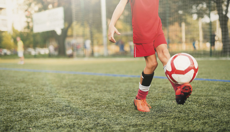 Young soccer player playing with soccer ball on field