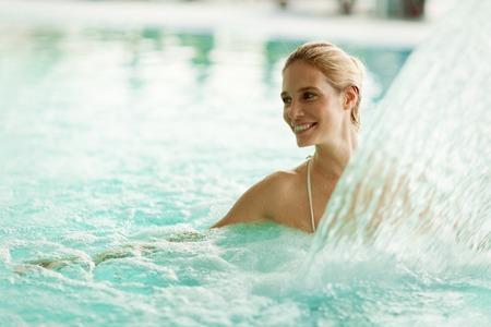 jet stream: Beautiful woman enjoying jet of water in spa  resort