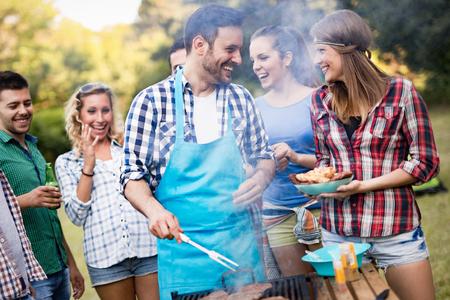 焼きながら、楽しんで幸せな友人のバーベキュー屋外パーティー 写真素材