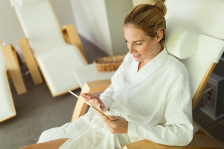 Woman relaxing in gown at spa resort on massage bed Stock Photo