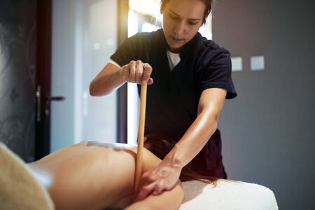 Masseur giving massage therapy to masseuse at wellness resort Stock Photo