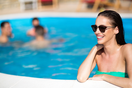 Portrait of beautiful happy woman by the swimming pool