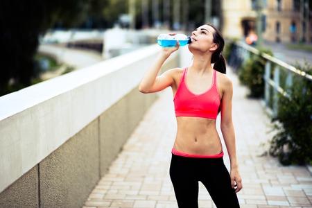 Thirsty beautiful sportswoman doing her jogging training Stock Photo