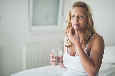 Beautiful pregnant woman taking pills for morning nausea