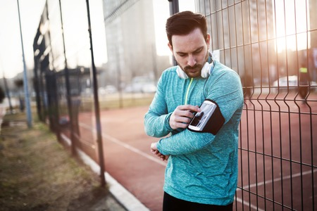 Handsome jogger listening to music while exercising Stock Photo