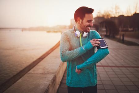 音楽を楽しみながら運動ハンサムな健康的なスポーツマン