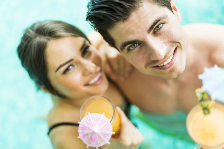 Portrait of a beautiful young couple smiling and drinking a cocktail in a pool Reklamní fotografie