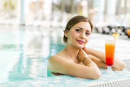 Mooie vrouw in een pool met een cocktail naast haar Stockfoto - 77368618