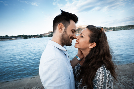 Beautiful romantic couple smiling and kissing outdoors
