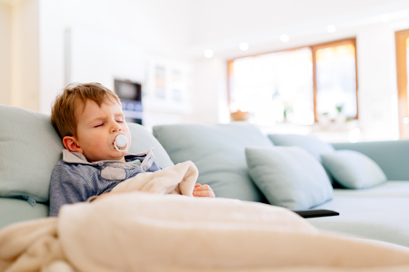 Sick child resting while wrapped in blanked Stock Photo