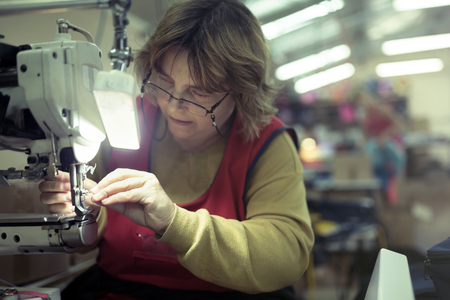 Worker in textile industry sewing on machine Stock Photo - 75802920