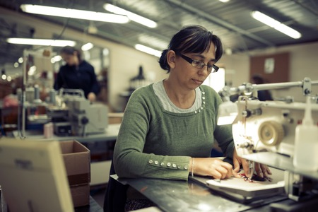 Worker in textile industry sewing on machine
