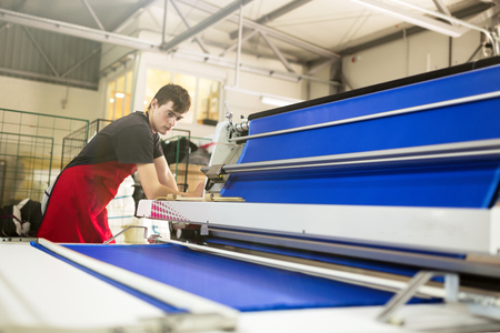 Worker working on fabric spreading machine in fabric industry Stock Photo - 75711992