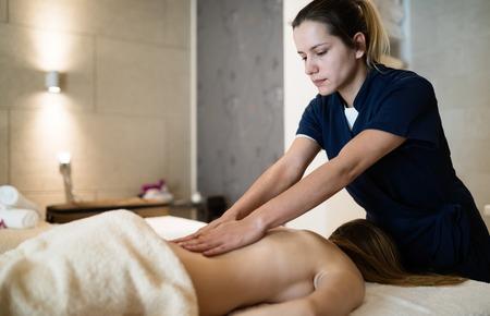 Masseur massaging back of female in spa resort Stock Photo