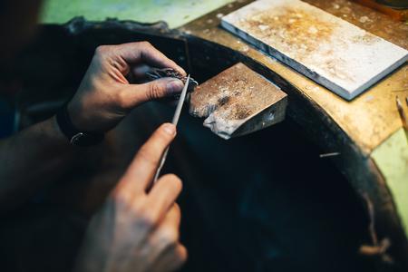 Jeweler polishing jewelry with tools Stock Photo