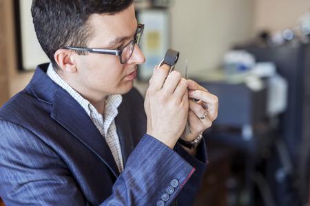 Jeweler examining diamond thoroughly through loupe Imagens