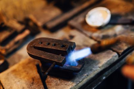 Jeweler using tourch to heat welding tools to proper temperature Imagens