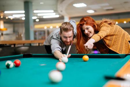 Beautiful happy couple playing billiards Stock Photo