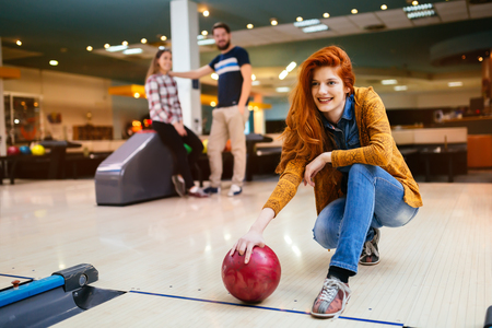 Beautiful woman bowling with friends getting ready to throw ball