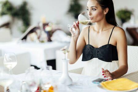 degustation: Beautiful woman tasting wine while sitting in restaurant