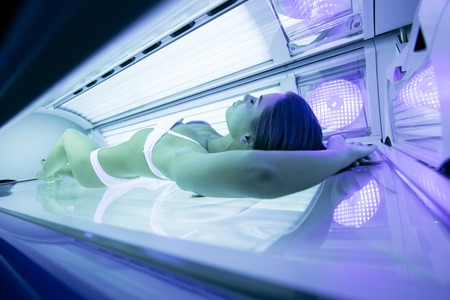 Beautiful sexy woman tanning in solarium Фото со стока