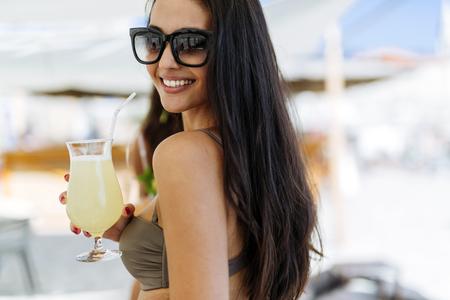 Mooie jonge vrouw het drinken van een cocktail en lachend