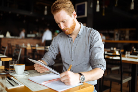 Businessman taking notes in cafe and writing down ideas Stock Photo