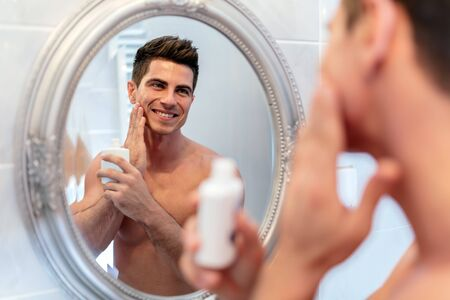 Handsome man looking in mirror after shaving