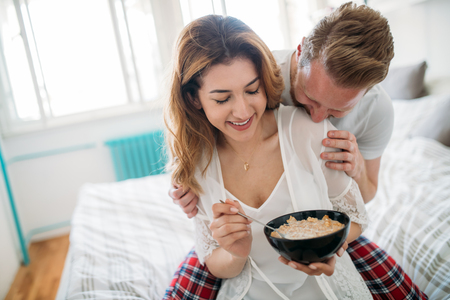 nightwear: Beautiful happy and romantic  couple waking up smiling in bedroom