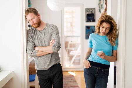 Paar met argumenten thuis en gefrustreerd met relatie Stockfoto