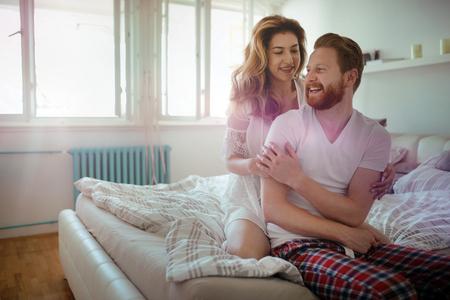 美しい幸せとロマンチックなカップルの寝室に笑みを浮かべて目を覚ます