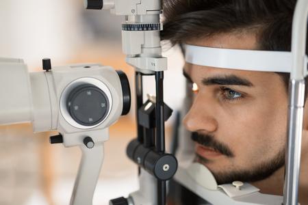 Patient or customer at slit lamp at optometrist or optician examining eyesight