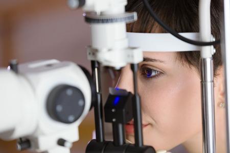 Vrouw controleert het gezichtsvermogen in een kliniek. Oogheelkunde. Geneeskunde en gezondheidsconcept.