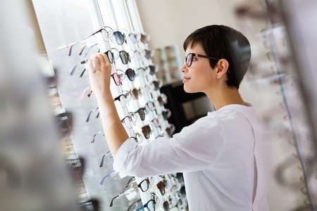 health care, eyesight and vision concept - happy beautiful woman choosing glasses at optics store Stockfoto