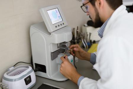 Optician repairing and fixing eye glasses at optical store Фото со стока - 77743547