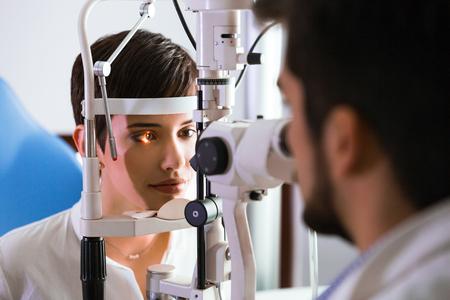 Optometrista verificando la vista del paciente y sugiriendo tratamientos de corrección de la visión Foto de archivo - 77743602