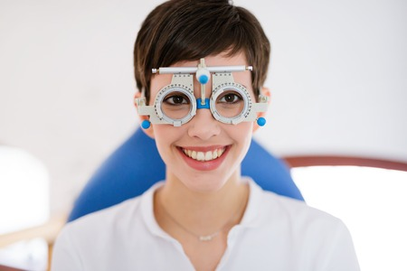 oculista: Beautiful woman doing eye test with optometrist in medical center
