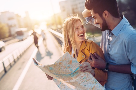 Smiling tourist couple in love traveling with map outdoors Stock Photo