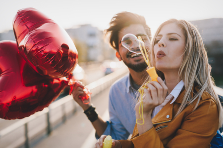 Happy couple in love dating and smiling while blowing bubbles Stock Photo