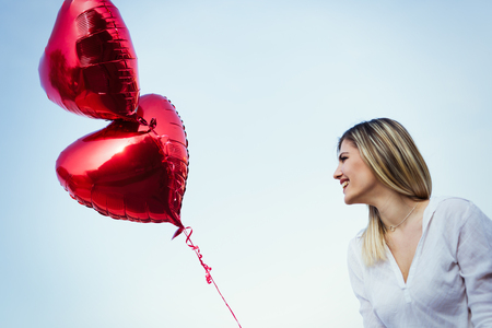 heart shaped: beautiful young woman with a heart-shaped balloon outdoor