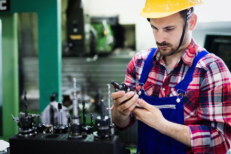 Portrait of an handsome engineer working in metal industry factory