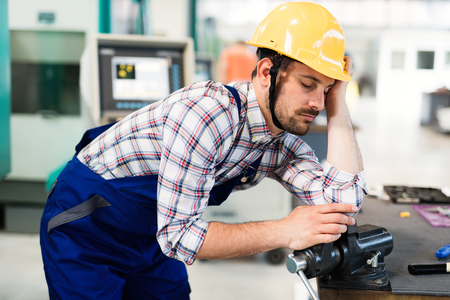 Tired overworked worker falls asleep during working hours in factory Imagens