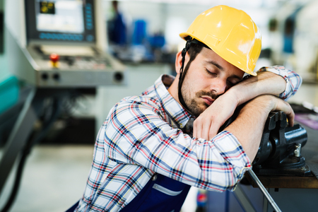 Tired overworked worker falls asleep during working hours in factory Stock Photo