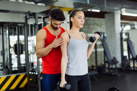 barbel: Young adult woman working out in gym with trainer