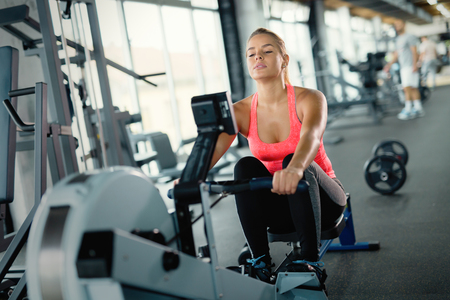 Young cute woman doing exercises with rowing machine Imagens