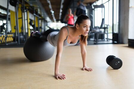 Young woman exercising with swiss ball in gym