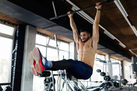 Young man performing hanging leg raises exercise