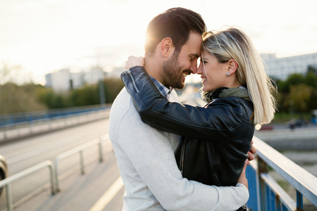 Happy young couple hugging and kissing on bridge Stock Photo